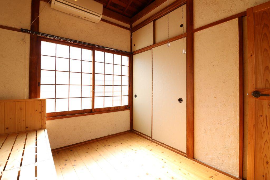 ベッドとベランダに続く南向き窓 (Room202)
